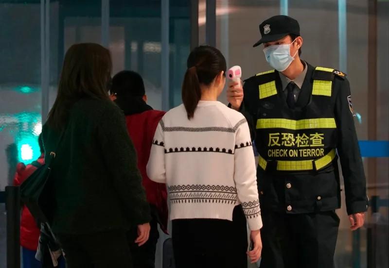 Nhân viên sân bay sử dụng máy đo nhiệt để kiểm tra hành khách rời khỏi sân bay quốc tế Thiên Hà tại TP Vũ Hán (Ảnh: AP)