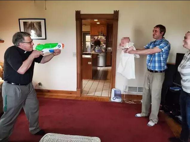 Linh mục dùng súng phun nước để rửa tội cho các bé sơ sinh trong mùa dịch Covid-19