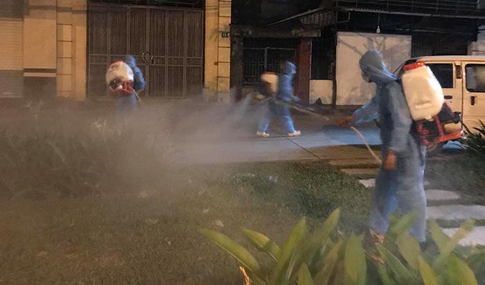 Cán bộ, nhân viên y tế phun khử khuẩn ở xung quanh đoạn đường đã phong tỏa ở số 36 Ngô Quyền.